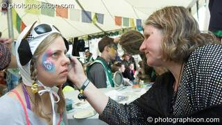Portrait of a Green Police officer as they prepare their costume, with face painting by Simone Kay & her team, at Glastonbury Festival 2008. Pilton, Great Britain. © 2008 Photographicon