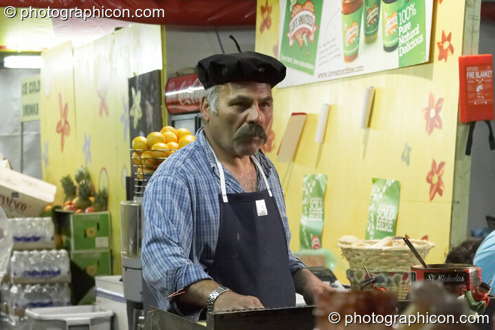 A man in a beret prepares food on a cafe stall at Glastonbury Festival 2008. Pilton, Great Britain. © 2008 Photographicon