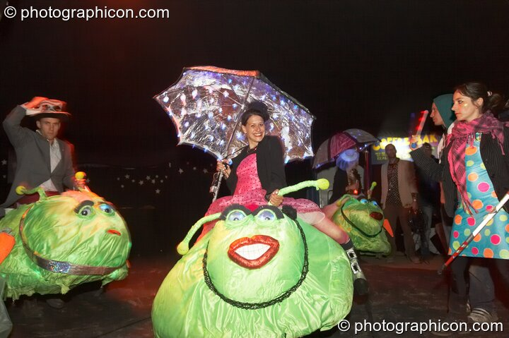 A walkabout group of people riding on big bugs at Glastonbury Festival 2008. Pilton, Great Britain. © 2008 Photographicon
