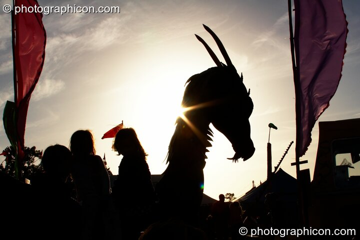 Silhouetted against the setting sun, children play on a dragon sculpture in the Green Roadshow Field at Glastonbury Festival 2008. Pilton, Great Britain. © 2008 Photographicon