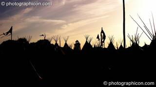 Silhouetted against the setting sun, the distant Park Tower nestles amongst tipis in the Tipi Village at Glastonbury Festival 2008. Pilton, Great Britain. © 2008 Photographicon