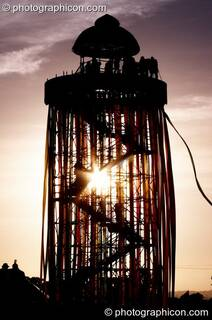Silhouetted against the setting sun, a tall decorated scaffold tower with viewing platform rises above The Park at Glastonbury Festival 2008. Pilton, Great Britain. © 2008 Photographicon