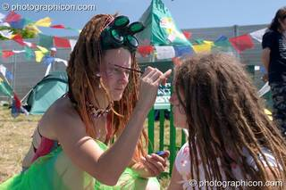 One woman wearing welding glasses paints the face of another at Glastonbury Festival 2004. Pilton, Great Britain. © 2004 Photographicon