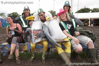 The Green Police pose with people in duck costume sitting on a bench at Glastonbury Festival 2007. Pilton, United Kingdom. © 2007 Photographicon
