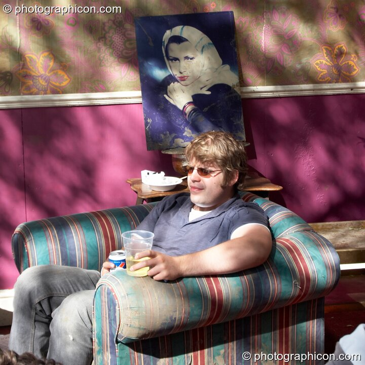 Man relaxing in an armchair in the tree house at the Secret Garden Party 2006. Huntingdon, Great Britain. © 2006 Photographicon