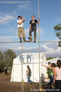 Two men stand on top of staffold poles at the Secret Garden Party 2006. Huntingdon, Great Britain. © 2006 Photographicon