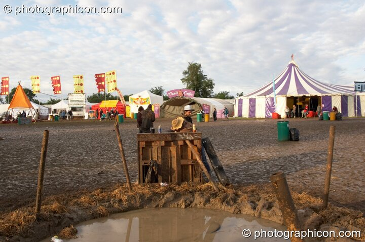 A group of friends jam on a wonky piano next to a pond in the early morning mud at the Secret Garden Party 2007. Huntingdon, Great Britain. © 2007 Photographicon