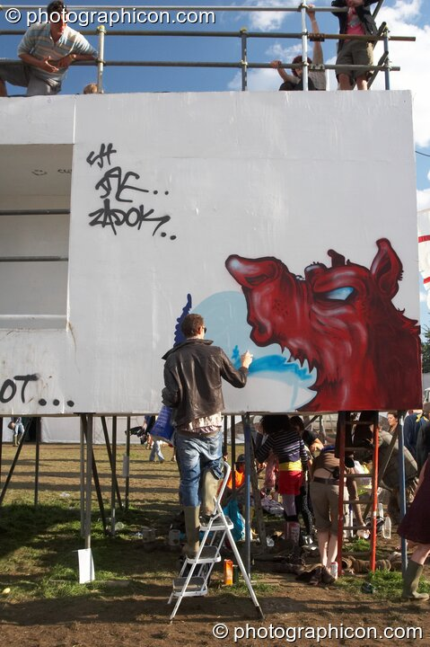 A graffiti artist paints The Tower at the Secret Garden Party 2007. Huntingdon, Great Britain. © 2007 Photographicon