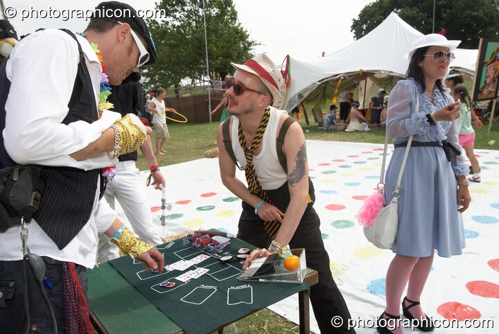 A man plays cards on a small table at the Secret Garden Party 2008. Huntingdon, Great Britain. © 2008 Photographicon