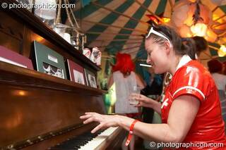 A woman plays the piano in a late night bar at the Secret Garden Party 2008. Huntingdon, Great Britain. © 2008 Photographicon