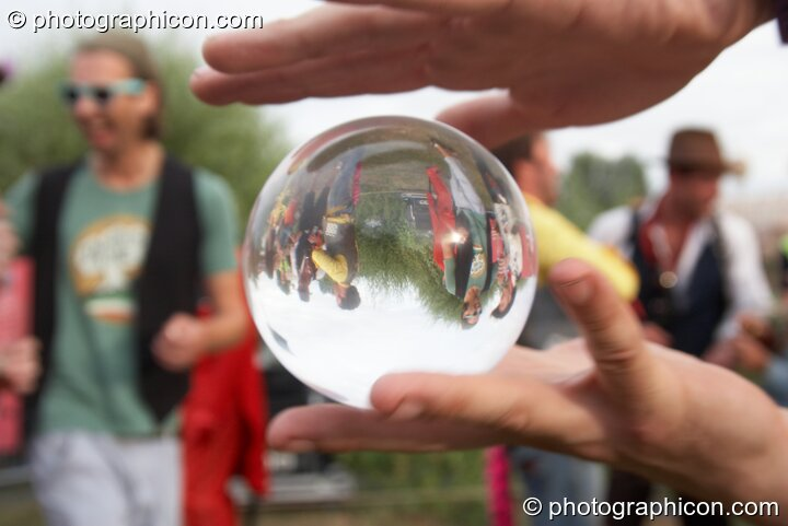 A smal crowd viewed through a clear plastic contact ball at the Secret Garden Party 2010. Huntingdon, Great Britain. © 2010 Photographicon