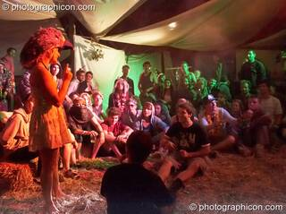 A woman wearing a wonky bird hat presides over a tag wrestling game in the Artful Badgers tent at the Secret Garden Party 2010. Huntingdon, Great Britain. © 2010 Photographicon