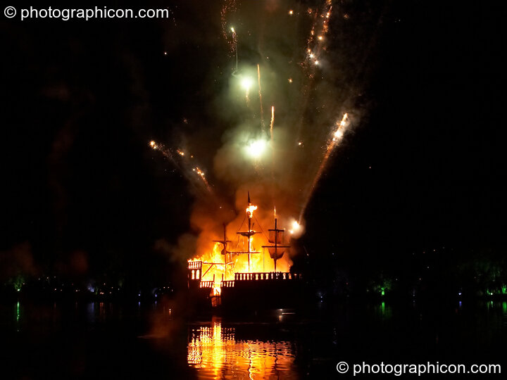 Fireworks erupt aboard the burning Galleon ship on the lake at the Secret Garden Party 2008. Huntingdon, Great Britain. © 2008 Photographicon