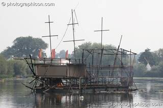 The burned out metal frame of the Galleon ship on the lake at the Secret Garden Party 2008. Huntingdon, Great Britain. © 2008 Photographicon