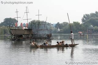 A punt makes an early morning trip to the burned out Galleon ship on the lake at the Secret Garden Party 2008. Huntingdon, Great Britain. © 2008 Photographicon