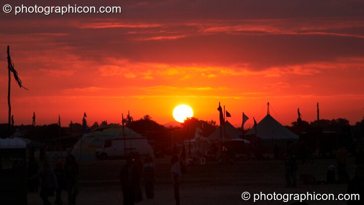 The sun rises over the festival site one day before summer solstice at Sunrise Celebration 2006. Yeovil, Great Britain. © 2006 Photographicon