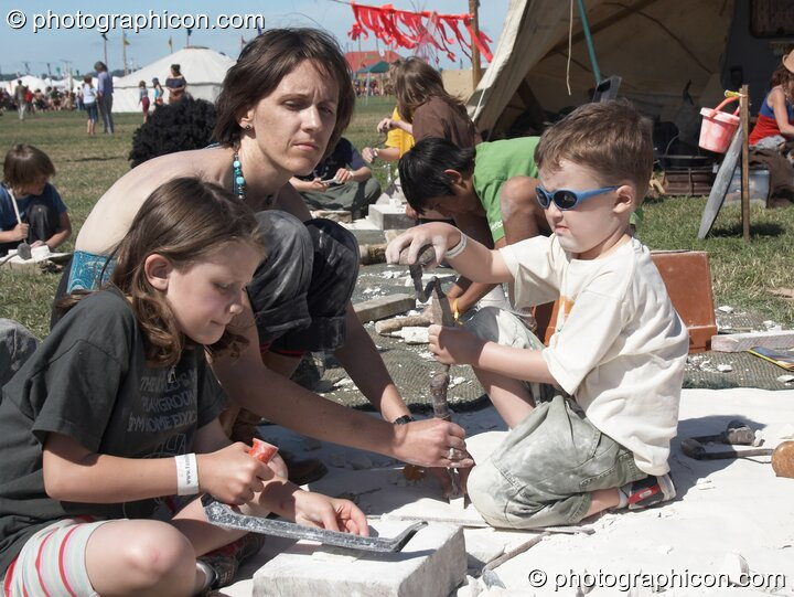 A mother supervises while her children enjoy masonic play with chalk blocks in the Crafts Field at Sunrise Celebration 2007. Yeovil, Great Britain. © 2007 Photographicon