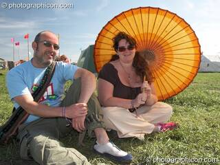 A man a woman sit with a parasol at Sunrise Celebration 2007. Yeovil, Great Britain. © 2007 Photographicon