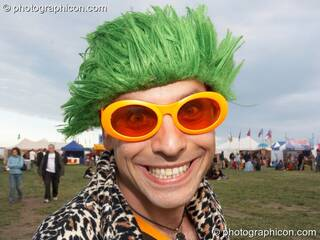 A man dressed to smile in lumo glasses and a green wig at Sunrise Celebration 2007. Yeovil, Great Britain. © 2007 Photographicon