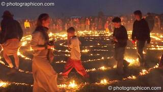 People walk the path through the blazing Green Dragon fire labyrinth at Sunrise Celebration 2007. Yeovil, Great Britain. © 2007 Photographicon