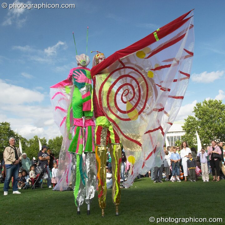Women wearing bright winged costumes gracefully dance on stilts at the Thames Festival 2004. London, Great Britain. © 2004 Photographicon
