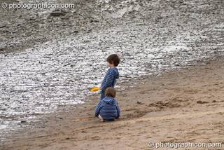 Two small boys play at a Reclaim The Beach party on the sandy river bank at the Thames Festival 2004. London, Great Britain. © 2004 Photographicon