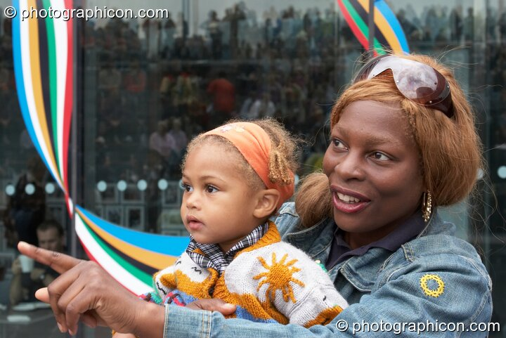 Profile of an Afro-Caribean mother and baby daughter watching a performance at the Thames Festival 2005. London, Great Britain. © 2005 Photographicon