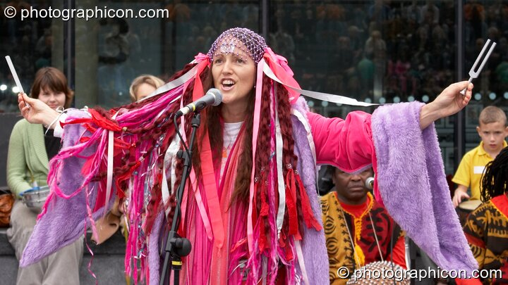 Ashera Hart resonates two tuning forks and sings in a performance with Drum4Africa, a fundraising project for African children, at the Thames Festival 2005. London, Great Britain. © 2005 Photographicon