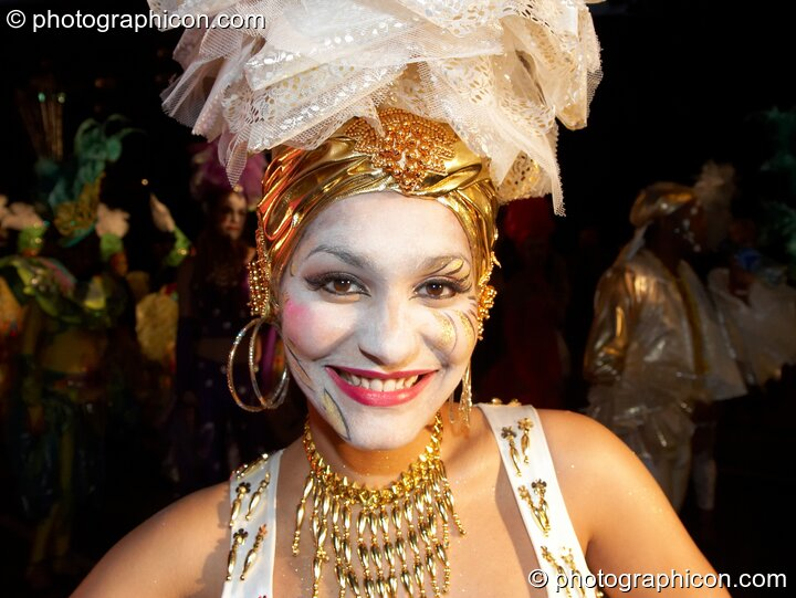 Woman with while face, gold jewellery and tall layer-hat smiles during the carnival at the Thames Festival 2005. London, Great Britain. © 2005 Photographicon