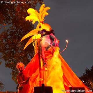 Person in big bird costume bathed in coloured light stips on top of Mandinga Arts' carnival float at the Thames Festival 2005. London, Great Britain. © 2005 Photographicon