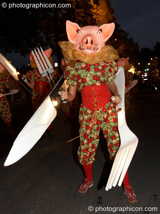 Person dressed as a pig carrying a very large plastic knif and fork during the carnival at the Thames Festival 2005. London, Great Britain. © 2005 Photographicon