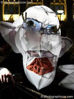Person wearing a large paper carnival mask of disfigured head at the Thames Festival 2005. London, Great Britain. © 2005 Photographicon