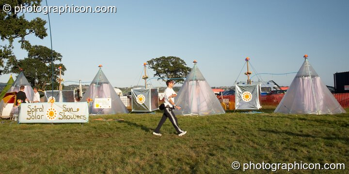 A man walks past the solar showers at Waveform Project 2007. Kenton, Exeter, Great Britain. © 2007 Photographicon