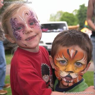 Small boy with face professionally pained as a tiger being hugged by his sister at Kingston Green Fair 2004. Kingston Upon Thames, Great Britain. © 2004 Photographicon