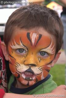 Small boy with face professionally pained as a tiger at Kingston Green Fair 2004. Kingston Upon Thames, Great Britain. © 2004 Photographicon