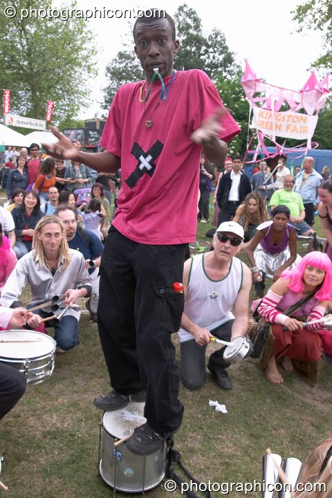 The leader of Rhythms of Resistance stands on his drum and shrugs at Kingston Green Fair 2004. Kingston Upon Thames, Great Britain. © 2004 Photographicon