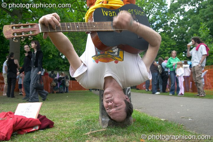 Ivan Inversion plays hanging upside-down at Kingston Green Fair 2005. Kingston Upon Thames, Great Britain. © 2005 Photographicon