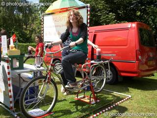Woman on pedal powered smoothie maker at Kingston Green Fair 2006. Kingston upon Thames, Great Britain. © 2006 Photographicon