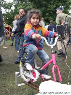 A girl inflates a pedal-powered model provided by The Campaign for Real Events at Kingston Green Fair 2006. Kingston upon Thames, Great Britain. © 2006 Photographicon