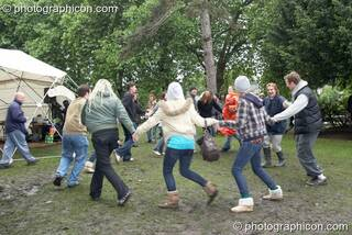 A happy group of young people dance in a circle despite the mud and rain at Kingston Green Fair 2007. Kingston upon Thames, Great Britain. © 2007 Photographicon
