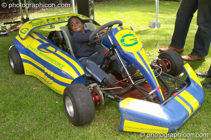 Small girl drives a Green Motorsport electric vehicle at the London Green Lifestyle Show 2005. Great Britain. © 2005 Photographicon