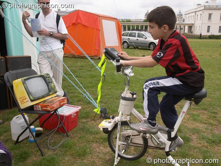A boy pedals to generate power for an old-style TV video game at the London Green Lifestyle Show 2005. Great Britain. © 2005 Photographicon