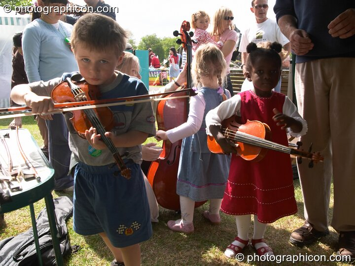 Children play with a instruments provided by Surrey Strings at the London Green Lifestyle Show 2005. Great Britain. © 2005 Photographicon