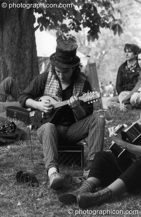 A man plays a relaxing tune under a tree at the first Kingston Green Fair in 1987. Kingston upon Thames, Great Britain. © 1987 Photographicon