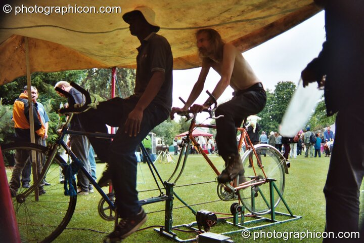 Two mwn on a bicycle generator providing power to a small music stage at Kingston Green Fair 2002. Kingston upon Thames, Great Britain. © 2002 Photographicon