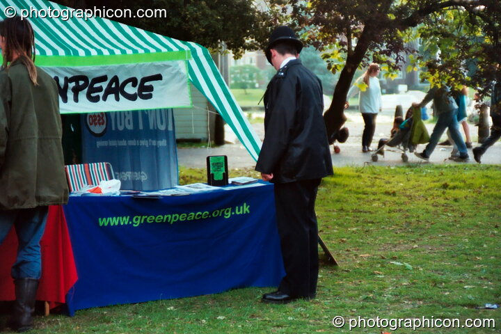 A policeman reading litrature on the Green Peace stall at Kingston Green Fair 2002. Kingston upon Thames, Great Britain. © 2002 Photographicon