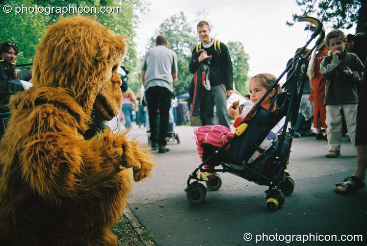 Man in gorilla costume talks to girl in push chair at Kingston Green Fair 2003. Kingston upon Thames, Great Britain. © 2003 Photographicon