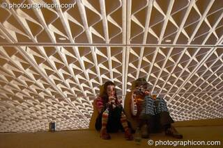 A couple sit in front of large projection of roofing girders at Dr Love's Psychoactive Explosion. London, Great Britain. © 2004 Photographicon