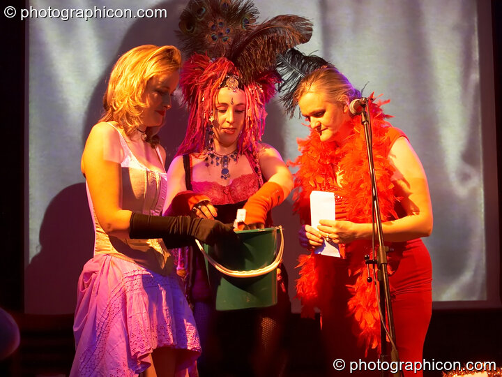 Ellie, Kwali, & Bernadette draw raffle tickets at the Save The World Club Burlesque Ball. Kingston upon Thames, Great Britain. © 2005 Photographicon
