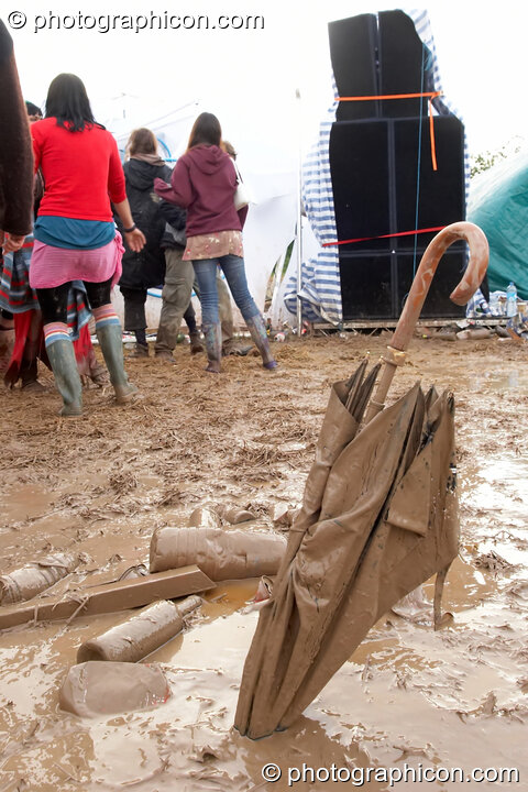 Trash amongst dancers in the mud outside the Little Green Planet Stage at the Echo Festival. Overton, Great Britain. © 2007 Photographicon